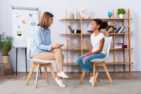 Photo for Smiling psychologist with digital tablet looking at african american girl sitting on chair during consultation in office - Royalty Free Image