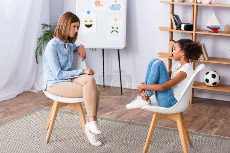 Psychologe betrachtet afrikanisch-amerikanische Mädchen, die Beine umarmen, während sie im Büro auf einem Stuhl sitzen