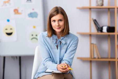 Positive Psychologin blickt in die Kamera, während sie auf einem Stuhl sitzt, mit verschwommenem Büro im Hintergrund