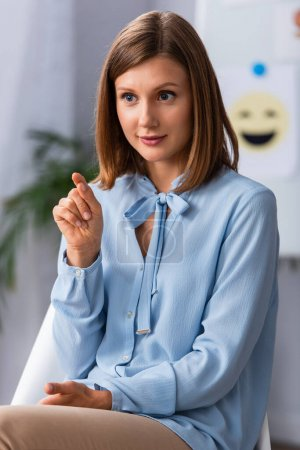 Photo for Positive female psychologist pointing with finger while sitting on chair in office on blurred background - Royalty Free Image