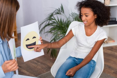 Photo for Smiling african american girl pointing with finger at happy expression on paper near psychologist on blurred foreground - Royalty Free Image