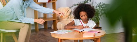 Photo for Psychologist pointing with finger at album near african american girl drawing with colored pencils on blurred foreground, banner - Royalty Free Image