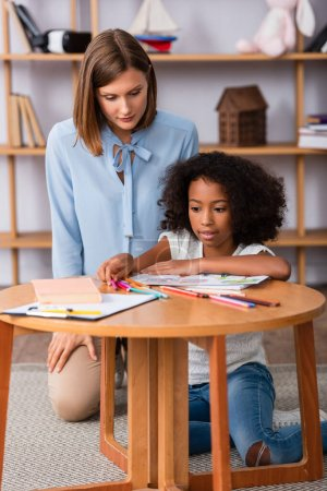 Photo for African american girl taking colored pencils on coffee table near psychologist sitting behind on blurred background - Royalty Free Image