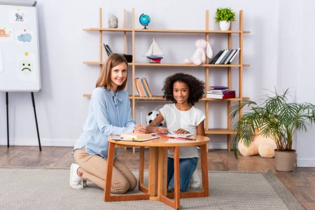 Full length of happy multicultural psychologist and girl looking at camera while sitting near coffee table in office