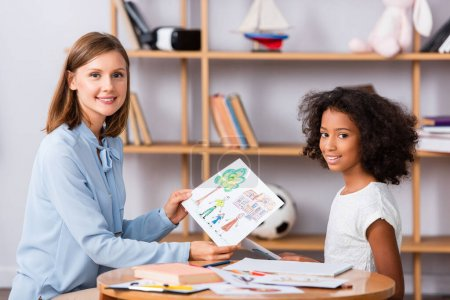 Photo for Smiling multicultural girl and psychologist with drawing looking at camera near coffee table with blurred shelves on background - Royalty Free Image