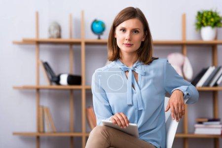 Photo pour Psychologue féminine positive avec tablette numérique regardant la caméra tout en étant assis sur une chaise sur fond flou - image libre de droit