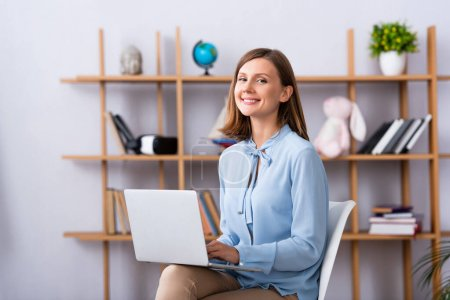 Photo for Happy psychologist looking at camera while using laptop in office on blurred background - Royalty Free Image