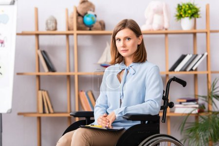 Photo for Disabled psychologist with clipboard looking at camera while sitting in wheelchair on blurred background - Royalty Free Image