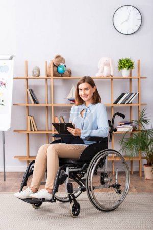 Full length of smiling psychologist with clipboard looking at camera while sitting in wheelchair in office