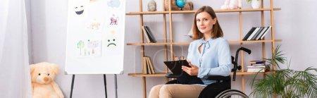 Positiver Psychologe mit Klemmbrett, der im Rollstuhl im Büro in die Kamera blickt, Banner