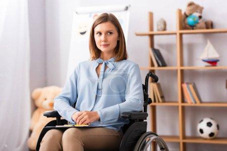 Photo pour Psychologue positif avec les mains serrées regardant loin tout en étant assis dans un fauteuil roulant avec un bureau flou sur fond - image libre de droit