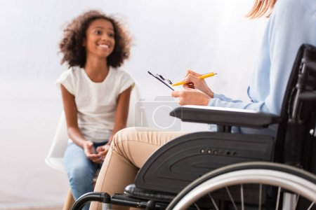 Photo pour Psychologue écrit sur presse-papiers tout en étant assis en fauteuil roulant avec une fille afro-américaine heureuse floue sur fond - image libre de droit