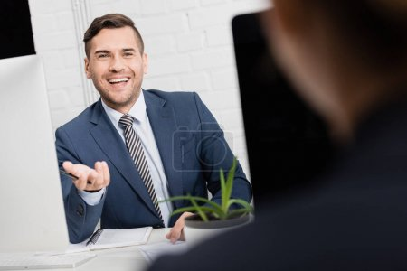 Photo for Happy executive gesturing, while sitting at workplace with blurred female co-worker on foreground - Royalty Free Image