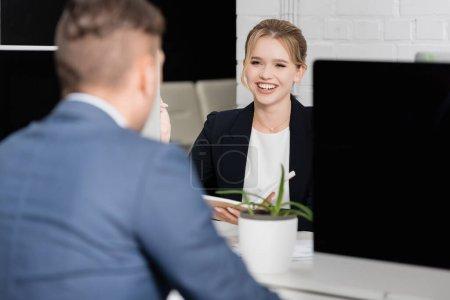 Photo pour Femme d'affaires blonde riant, tout en étant assis sur le lieu de travail avec un collègue flou au premier plan - image libre de droit