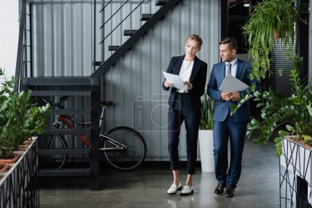 Businessman with laptop looking at paper sheets in hands of female colleague, while standing at work