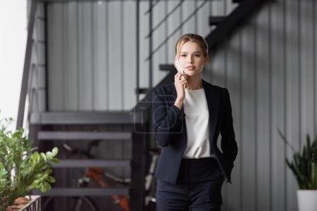 Photo pour Femme exécutive avec la main dans la poche détournant les yeux, tout en parlant sur un téléphone mobile sur fond flou - image libre de droit