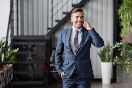Hombre de negocios sonriente con la mano en el bolsillo mirando hacia otro lado, mientras habla en el teléfono móvil en un fondo borroso