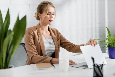 Blonde businesswoman closing laptop, while sitting at table in office on blurred foreground