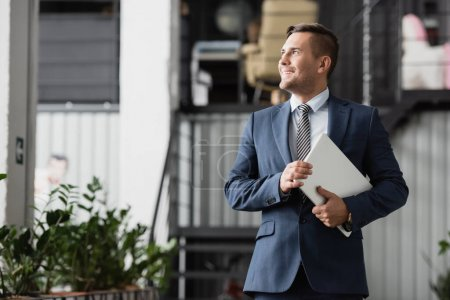 Photo for Smiling businessman with laptop looking away, while standing at work on blurred background - Royalty Free Image