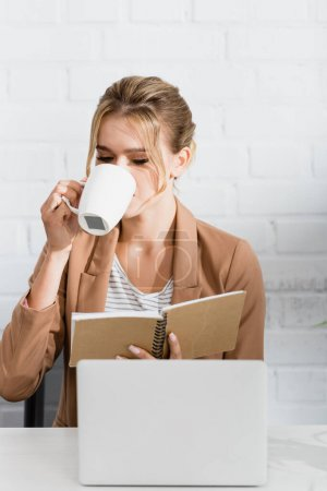 Businesswoman with notebook drinking from cup, while sitting at workplace with laptop