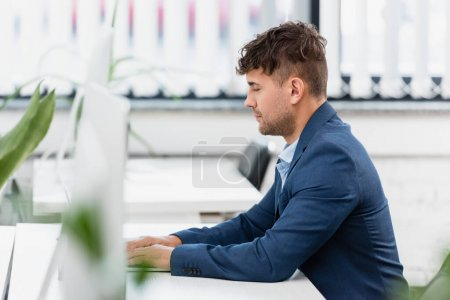 Photo for Executive working, while sitting at table in office with blurred plant on foreground - Royalty Free Image