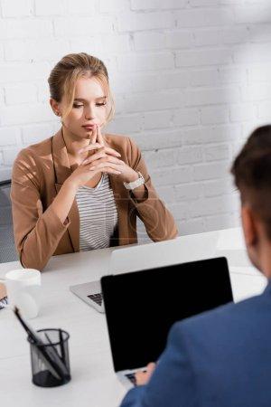 Photo pour Exécutif féminin réfléchi regardant ordinateur portable, tout en étant assis sur le lieu de travail avec un collègue flou au premier plan - image libre de droit