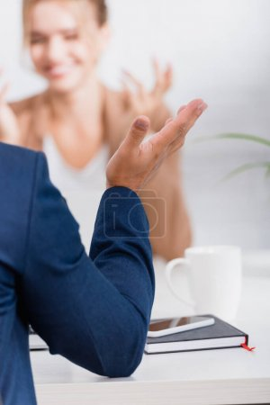 Close up view of businessman gesturing, while sitting at table on blurred background