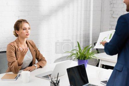Photo pour Geste exécutif féminin, tout en regardant le document dans les mains d'un collègue debout près du lieu de travail - image libre de droit