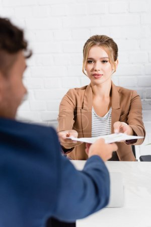 Blonde businesswoman taking document from colleague, while sitting at table on blurred foreground