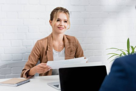 Photo for Smiling businesswoman with documents looking at co-worker, while sitting at table with laptops on blurred foreground - Royalty Free Image