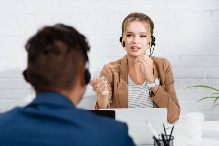 Female consultant in headset gesturing, while sitting at workplace on blurred foreground