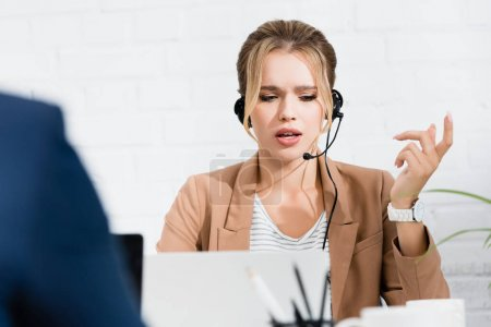 Serious woman in headset gesturing, while sitting near laptop at workplace on blurred foreground