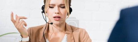 Photo pour Consultante sérieuse dans un casque gestuel au premier plan flou, bannière - image libre de droit