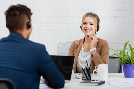 Happy woman in headset looking at camera, while sitting at workplace with digital devices on blurred foreground