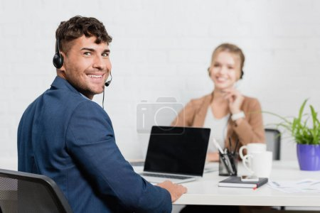 Call center operator in headset looking at camera, while sitting at workplace with digital devices on blurred background