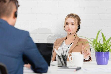 Femme sérieuse dans le casque regardant son collègue, alors qu'elle était assise sur le lieu de travail sur le premier plan flou