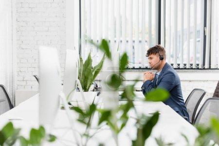 Photo pour Opérateur sérieux dans casque assis sur le lieu de travail dans le bureau avec usine floue au premier plan - image libre de droit