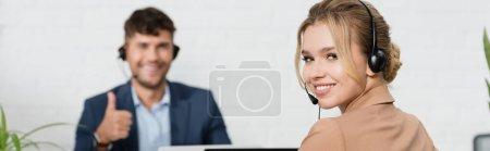 Photo pour Opérateur féminin souriant dans un casque regardant la caméra avec un collègue flou en arrière-plan, bannière - image libre de droit