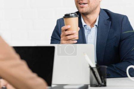 Photo pour Vue recadrée du travailleur de bureau avec tasse en papier parlant, assis à table avec des ordinateurs portables sur le premier plan flou - image libre de droit