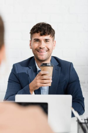 Smiling businessman with paper cup looking at colleague, while sitting at workplace on blurred foreground