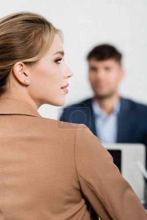 Back view of blonde businesswoman looking away with blurred co-worker on background