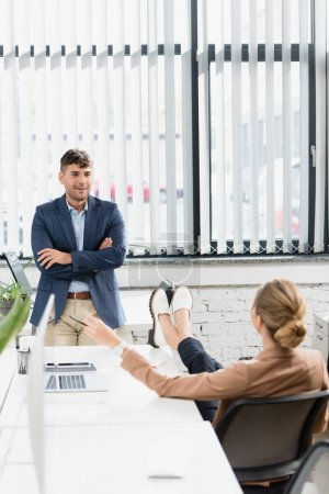 Back view of businesswoman with crossed legs sitting at office chair near colleague during break in office on blurred foreground
