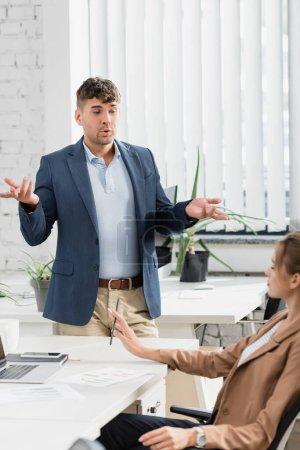 Geschäftsmann gestikuliert, während er mit einem Kollegen spricht, der in der Pause am Arbeitsplatz sitzt