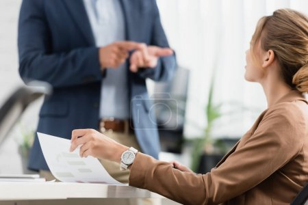 Female executive with document sitting at table with blurred colleague gesturing on background