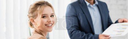 Photo pour Joyeux exécutif féminin regardant la caméra avec un collègue flou sur fond, bannière - image libre de droit