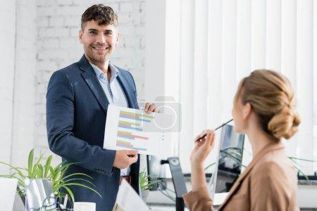 Photo pour Homme d'affaires souriant regardant la caméra, tout en montrant une feuille de papier avec des graphiques près du lieu de travail sur le premier plan flou - image libre de droit