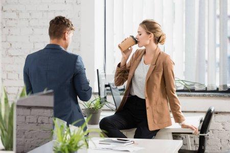 Rückansicht eines Geschäftsmannes, der in der Pause neben einer Kollegin steht und Kaffee trinkt