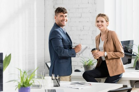 Smiling businesspeople looking at camera during break in office