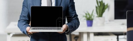 Cropped view of executive in formal wear showing laptop with blank screen with blurred office on background, banner