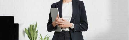 Photo for Cropped view of businesswoman in formal wear holding laptop near plants and computer monitors, banner - Royalty Free Image